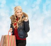 happiness, winter holidays, christmas and people concept - smiling young woman in winter clothes with shopping bags over blue lights background