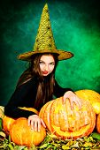 Pretty teen girl in a costume of witch standing with pumpkins over dark smoky background. Halloween.