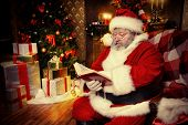 Santa Claus sitting in a room decorated for Christmas, and carefully read the boojk. Christmastime.