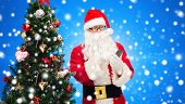 holidays, technology and people concept - man in costume of santa claus with smartphone and christmas tree over blue snowy background