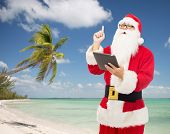 christmas, holidays, technology, travel and people concept - man in costume of santa claus with tablet pc computer pointing finger up over tropical beach background