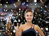 technology, communication, advertising and people concept - smiling woman in evening dress showing smartphone blank screen over snowy night city background