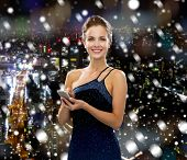 technology, christmas, holidays and people concept - smiling woman in evening dress holding smartphone over snowy night city background