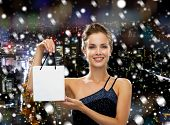 christmas, sale, advertisement, holydays and people concept - smiling woman with white blank shopping bag over snowy night city background