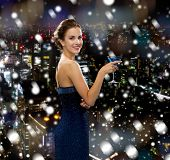drinks, holidays, christmas, people and celebration concept - smiling woman in evening dress holding cocktail over snowy night city background