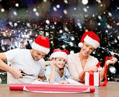 christmas, holidays, family and people concept - happy mother, father and little girl in santa helper hats with gift box and scissors over snowy night city background