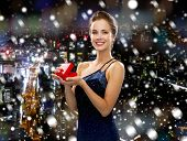 christmas, holidays and people concept - smiling woman in evening dress with small red gift box over snowy night city background