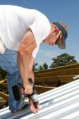 image of rafters  - Roofer construction worker uses a battery powered screwgun to fasten sheets of metal roofing to the rafters on top of a barn - JPG