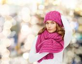 happiness, winter holidays, christmas and people concept - smiling young woman in pink hat and scarf over lights background