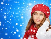 happiness, winter holidays, christmas and people concept - young woman in red hat and scarf over blue snowy background