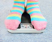 Overweight woman in funny socks standing on a retro style weighing machine.