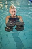 Portrait of a fit female swimmer working out with foam dumbbells in swimming pool at leisure centre