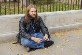 image of long beard  - Blond long hair and beard young adult hipster man listening music. Outdoor, urban scene. ** Note: Shallow depth of field - JPG