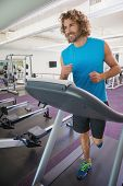 Smiling handsome man running on treadmill in the gym