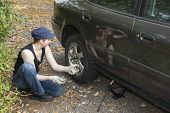 Young woman changing a tire crouching down at the side of the car