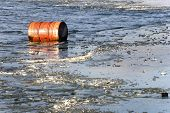 Oil barrel floating in icy water