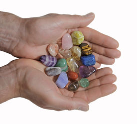 pic of wicca  - Male crystal therapist holding selection of crystals in open palms on white background - JPG