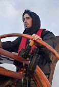 image of ship steering wheel  - Young sailor on a ship - JPG