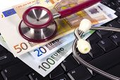picture of lobbyist  - costs for medicine and healthcare with euros and stethoscope over keyboard - JPG