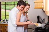 stock photo of she-male  - romantic young man hugging girlfriend while she cooks for breakfast - JPG
