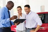picture of contract  - african car dealer explaining sales contract to couple buying a car - JPG