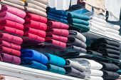 pic of department store  - colored shirts on a shelf in the store - JPG