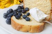 pic of pound cake  - Slice of pound cake with spoonfull of whipped cream with blueberries and flowers in the background - JPG