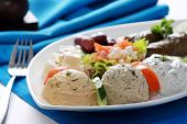 stock photo of greek food  - Greek vegetarian food mix pikilia with hummus tzatziki feta cheese dolmades and olives served in dish with fork aside - JPG
