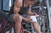 stock photo of bandage  - Muscular Caucasian man wraps knee with sport bandage in weightlifting gym - JPG