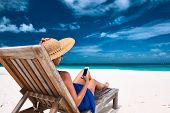 picture of beach hat  - Young woman in hat with mobile phone at the beach - JPG
