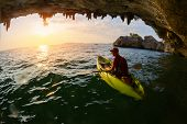 stock photo of cave woman  - Young lady sitting in the kayak near limestone cave - JPG