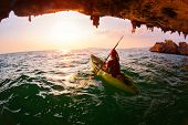 image of cave woman  - Young lady paddling the kayak from limestone cave towards open sea - JPG