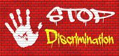 stock photo of racial discrimination  - stop discrimination no racism agains minorities equal rigths no homophobia or gender discrimination graffiti on red brick wall - JPG