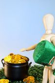 stock photo of pot gold  - A wooden mannequin directs the viewer to a pot of gold - JPG