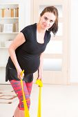 foto of belly-band  - Young pregnant woman exercising with stretch band at home - JPG