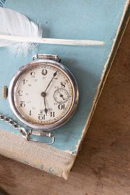 foto of politeness  - Old watches on a blue background and feather vintage - JPG