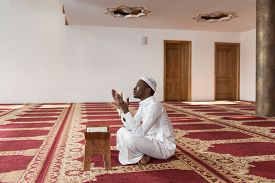 picture of muslim man  - African Muslim Man Making Traditional Prayer To God While Wearing A Traditional Cap Dishdasha [[** Note: Shallow depth of field ** Note: Visible grain at 100%, best at smaller sizes - JPG