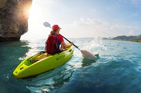 stock photo of kayak  - Young lady paddling the kayak near the cliff at sunny day - JPG