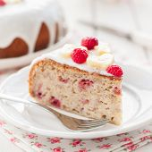 picture of banana  - A Piece of Banana Cake with Sugar Glaze Topped with Raspberries and Banana Slices square close up shallow dof  - JPG