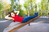 stock photo of crunch  - Girl is doing crunches on the wooden board at the sports ground during summer sunny day outside - JPG