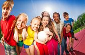 foto of volleyball  - Teens standing in hug on the volleyball game court holding ball during summer sunny day - JPG