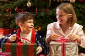 Children Opening Christmas Present In Front Of Tree