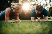 Fit Young Man And Woman Exercising In Park poster