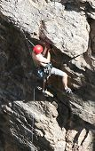 stock photo of sling bag  - A rock climber works his way up a rock face protected by a rope clipped into bolts. He is wearing a helmet and quickdraws dangle from his harness. The route is in the desert southwest United States. Mt Lemmon Arizona.
