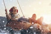 Happy child girl on swing in sunset winter. Little kid playing on a winter walk in nature. poster