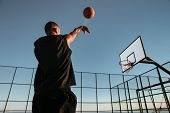 Portrait of a basketball player taking a jump shot on an outdoor basketball court poster