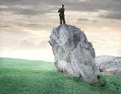 Empresário de pé sobre uma rocha e observando o panorama