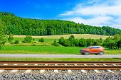 A Fast Moving Car Along The Road Goes Alongside The Railway Tracks poster