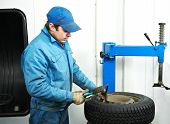 mechanic repairman making tyre fitting with compressed air