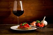 stock photo of red wine  - photo of delicious bruschetta appetizer with red wine glass on wooden table - JPG